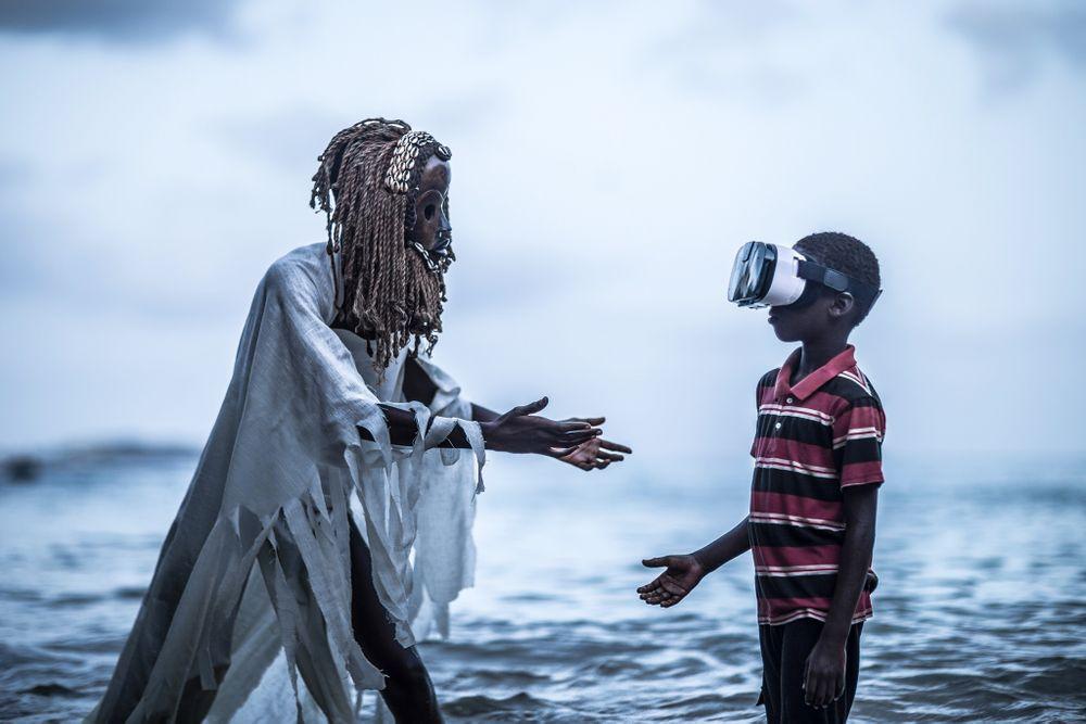 Kind mit VR Brille und Mann mit afrikanischer Maske